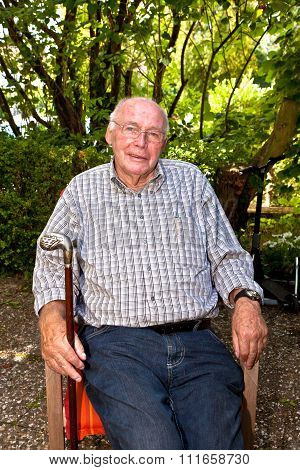 Elderly Man Sitting In A Chair In His Garden And Looks Very Friendly