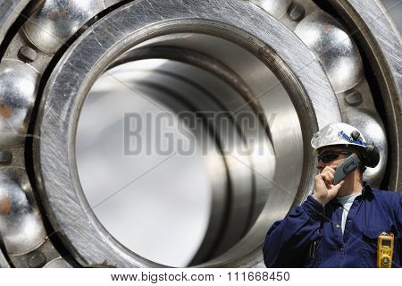 engineer, worker, talking in phone with giant ball-bearing in background, steel industrial
