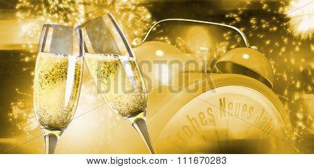 Champagne glasses clinking against colourful fireworks exploding on black background
