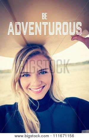 Motivational new years message against smiling woman in wet suit holding surfboard over head