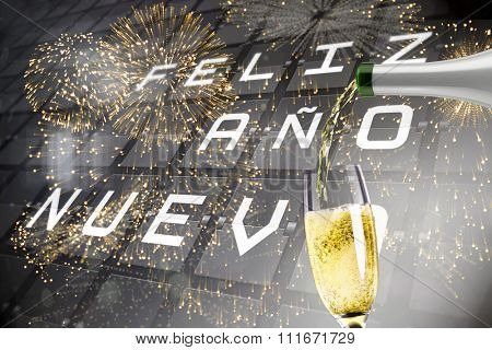 Champagne pouring against new year message on black roller board in spanish