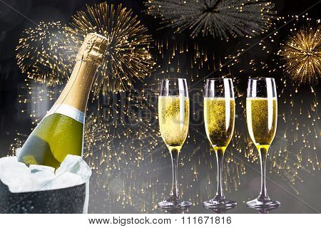 Champagne cooling in ice bucket against colourful fireworks exploding on black background