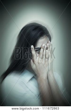 Portrait of woman peeking through fingers against grey vignette