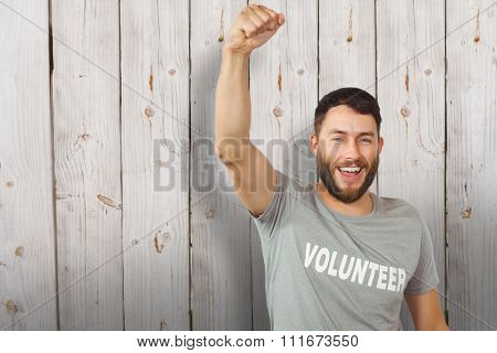 Portrait of cheerful volunteer against wooden background