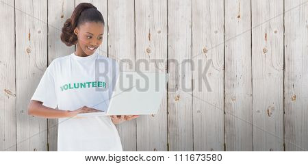 Happy volunteer using laptop against wooden background