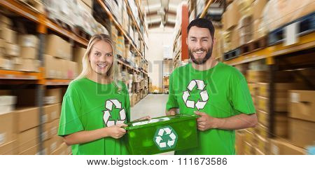 Portrait of smiling volunteers carrying recycling container against shelves with boxes in warehouse