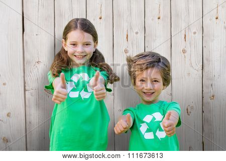 Happy siblings in green with thumbs up against wooden background