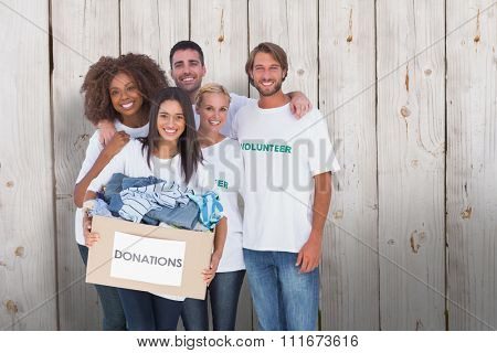 Smiling group of volunteers holding donation box against wooden background