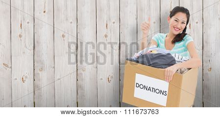 Woman with clothes donation gesturing thumbs up against wooden background