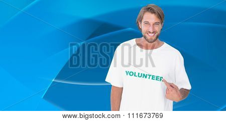 Smiling man pointing to his volunteer tshirt against abstract blue design
