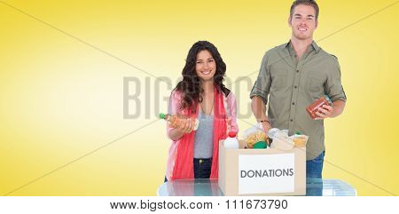 Smiling volunteers taking out food from donations box against yellow vignette