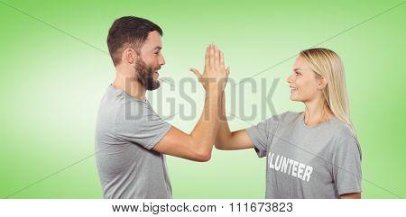 Smiling volunteer doing high five in office against green vignette