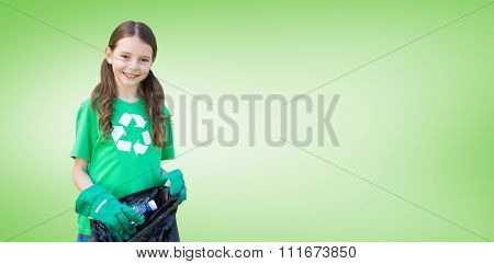 Happy little girl collecting rubbish against green vignette