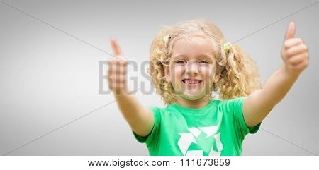 Happy little girl in green with thumbs up against grey vignette