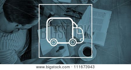 lorry against man writing while sitting by desk