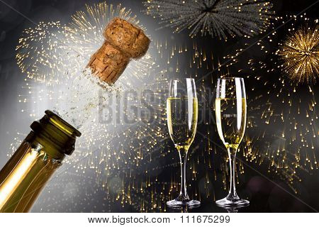 Close up of champagne cork popping against colourful fireworks exploding on black background