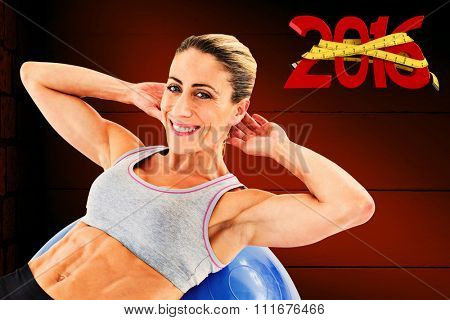 Fit woman doing sit ups on blue exercise ball smiling at camera against dark grey room