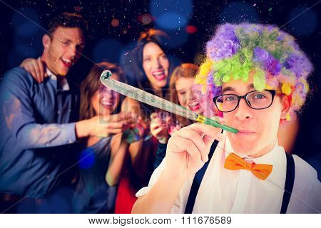 Geeky hipster wearing a rainbow wig blowing party horn against happy friends drinking shots smiling at camera