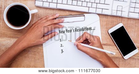New years resolution list against businesswoman writing on clipboard on desk