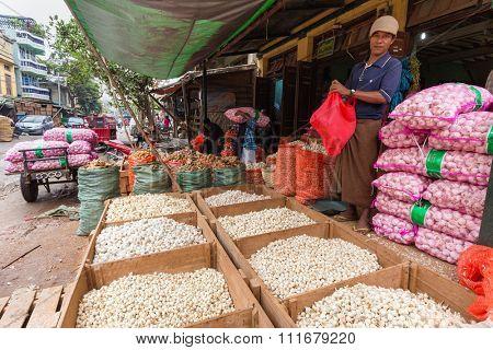 MANDALAY,MYANMAR,JANUARY 17, 2015: A man is selling tons of garlic in the central street market of Zegyo, in Mandalay, Myanmar (Burma).