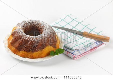 marble bundt cake, kitchen knife and checkered dishtowels on white background