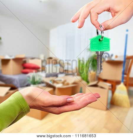 Hand with house key. Real estate and moving background.