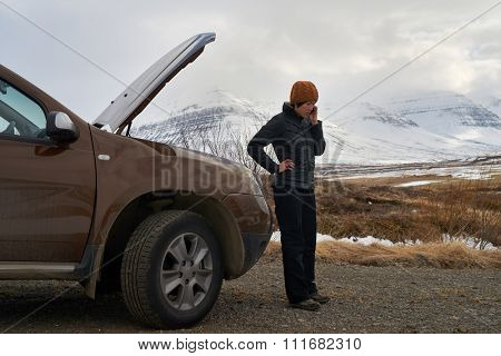 Asian woman with rental car breakdown engine trouble with hood up, calling with mobile phone for help, stranded in winter