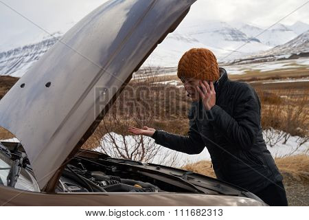 Asian woman with rental car breakdown engine trouble with hood up, calling with mobile phone for help, stranded in rural area
