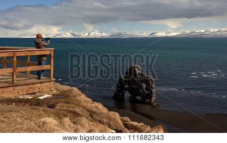 Tourist standing on wooden lookout point deck taking a photo of the Hvitserkur, beautiful rock formation on the coast snow capped mountains in background