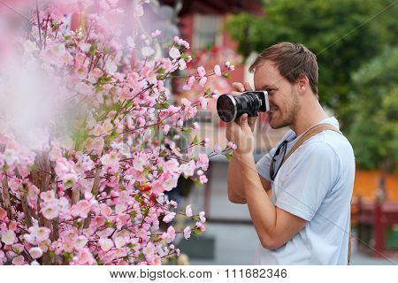 Caucasian tourist taking photo of blooming cherry plum blossom decoration for chinese new year in modern asian city
