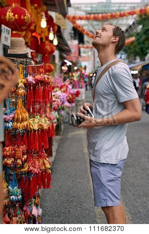 Tourist traveler with camera in asian city chinatown exploring cultural attractions and shopping for souvenir trinkets