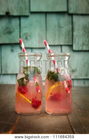 Two vintage bottles of pink lemonade with raspberry and mint standing on a wood background