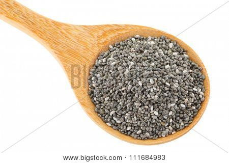 A wooden spoon full of dried Chia seeds (Salvia hispanica) isolated on white background