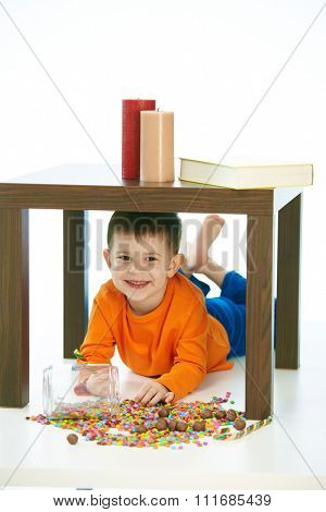 Cute caucasian kid lying under table with sweets jar spilled. Happy, smiling, isolated on white.