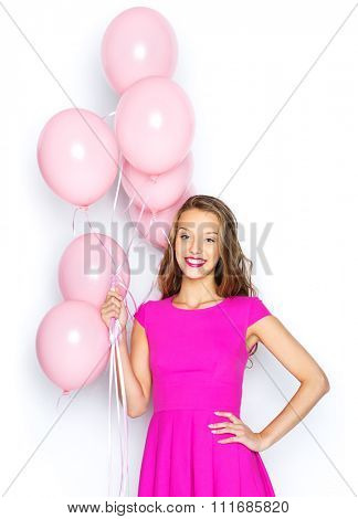 beauty, people, style, holidays and fashion concept - happy young woman or teen girl in pink dress with helium air balloons