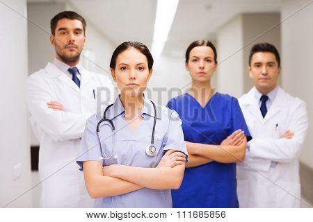 clinic, profession, people, health care and medicine concept - group of medics or doctors at hospital corridor