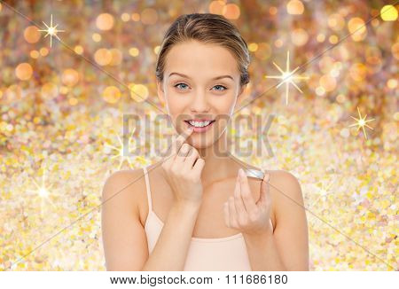 beauty, people and lip care concept - smiling young woman applying lip balm to her lips over golden glitter background
