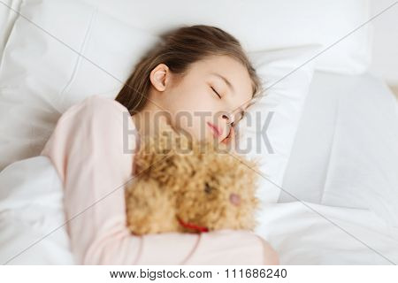 people, childhood, rest and comfort concept - girl sleeping with teddy bear toy in bed at home