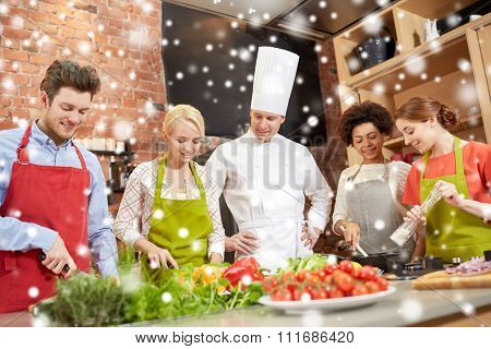 cooking class, culinary, food and people concept - happy group of friends with male chef cook cooking in kitchen over snow effect
