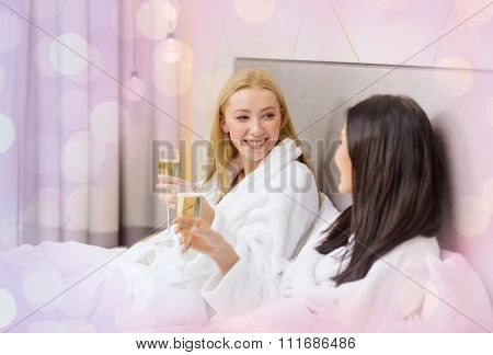 travel, friendship, bachelorette party and people concept - smiling girlfriends in bathrobes with champagne glasses in bed over holidays lights background