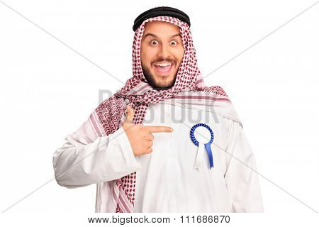 Joyful young Arab wearing an award ribbon on his robe and pointing towards it with his hand isolated on white background
