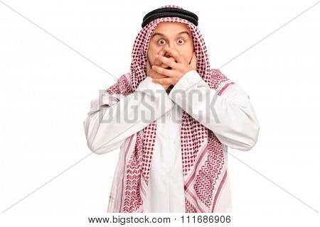 Shocked male Arab covering his mouth with his hands and looking at the camera isolated on white background