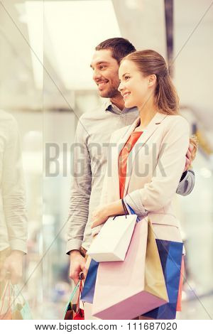 sale, consumerism and people concept - happy young couple with shopping bags looking to shop window in mall