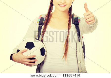 Teenager with foot ball and thumbs up.