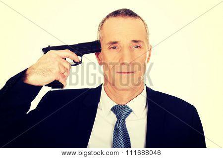 Portrait of a man with handgun near head.
