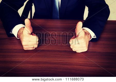 Closeup of businessman thumbs up on the desk.