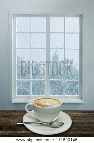 A cup of cappuccino and snowstorm view from the window on the background