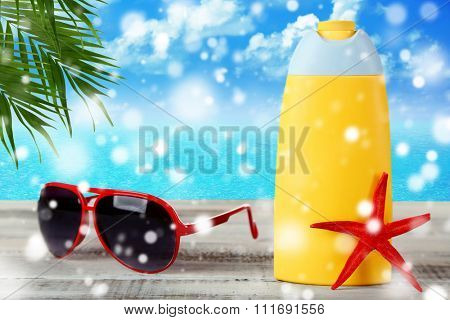 Bottle of suntan cream with sunglasses and sea star on table over snow effect