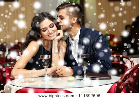 Young couple flirting at the restaurant over snow effect