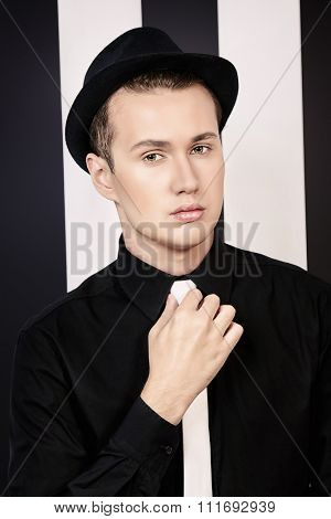 Elegant young man posing over backgroung of black and white stripes. Studio shot.